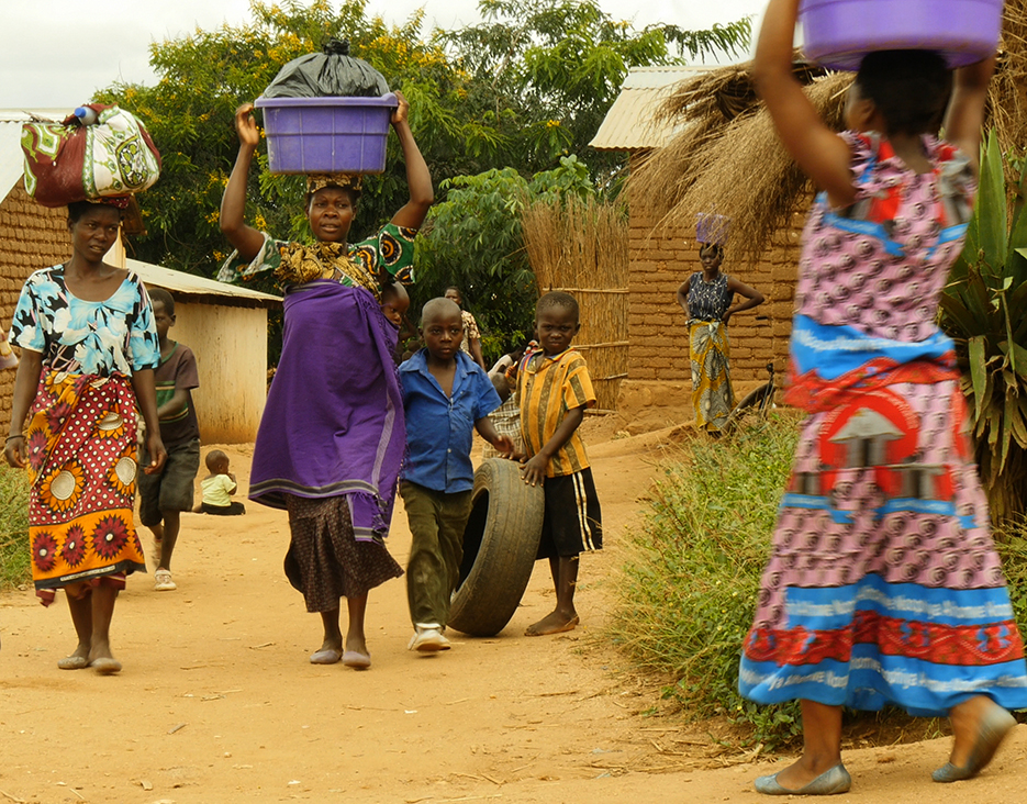 KAUMA VILLAGE, MALAWI (6/2/2015) -- Some residents tote buckets or goods on their heads as they walk through Kauma Village, located on the outskirts of Malawi's capital and largest city, Lilongwe. Habitat Malawi and a partner have established multiple water kiosks in the city to offer clean water to the public. Habitat has also helped with sanitary toilets and instructions about hygiene. Photo courtesy of Habitat for Humanity's Europe, Middle East and Africa office.